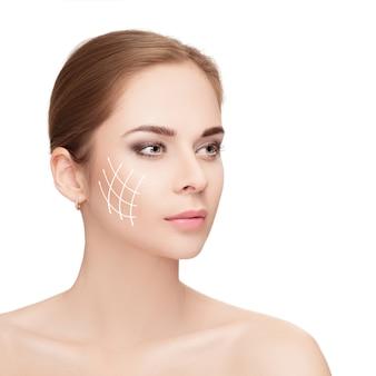 Spa portret atrakcyjnej kobiety ze strzałkami na twarzy na białym tle. koncepcja liftingu twarzy. chirurgia plastyczna, medycyna