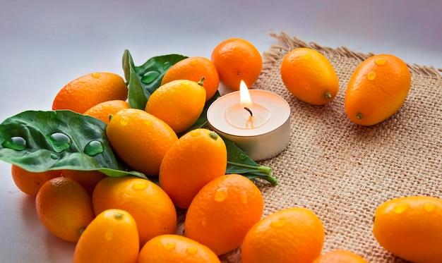 Spa składa się z zestawu liści mandarynki i świecy. białe tło. skopiuj miejsce