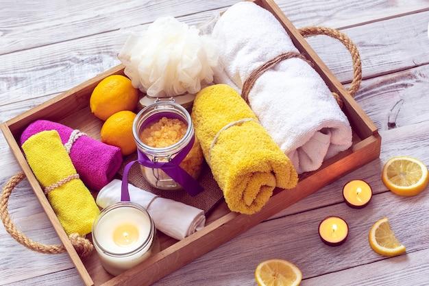 Spa składa się z żółtej soli morskiej, cytryn i innych akcesoriów do kąpieli na drewnianej tacy