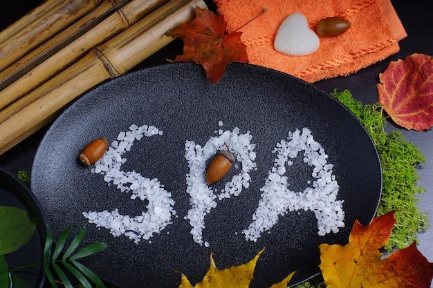 Spa słowo napisane na talerzu obok jesiennych liści i bambusa