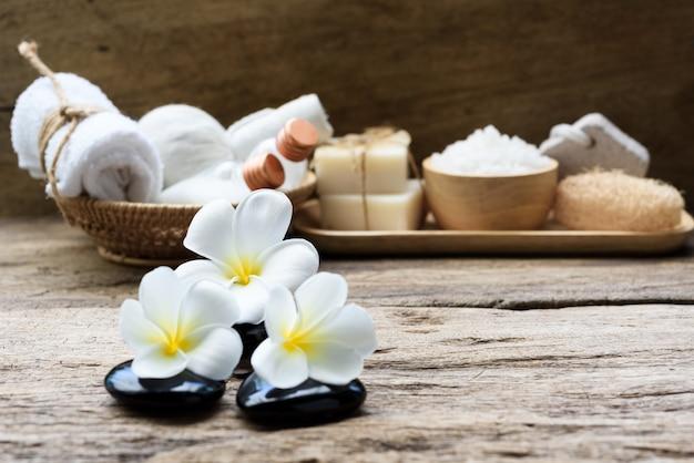 Spa wellness koncepcja, biała świeca, mleko z mydłem, sól, ręcznik, kwiaty i ziołowa piłka do masażu na białym stole z drewna z zielonym stawem