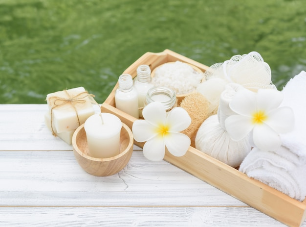 Spa wellness koncepcja, biała świeca, mleko z mydłem, sól, ręcznik, kwiaty i ziołowa piłka do masażu na białym stole z drewna