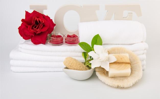 Spa wellness z czerwoną różą, białym ręcznikiem, mydłem mlecznym i muszlą na białym tle