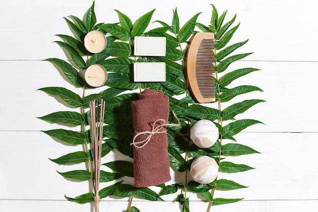 Spa zestaw z ręcznikiem i mydłem na białym tle drewnianych z zielonymi liśćmi. widok z góry. skopiuj miejsce. martwa natura. makieta. płaskie ułożenie