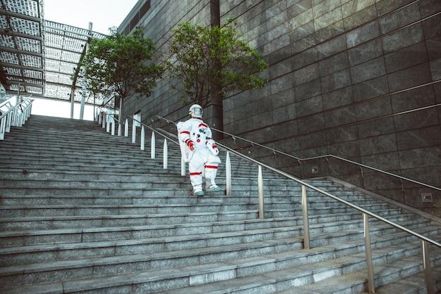 Spaceman na futurystycznej stacji mężczyzna w skafandrze kosmicznym spacerujący po mieście