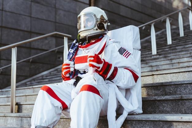 Spaceman na futurystycznej stacji. mężczyzna w skafandrze kosmicznym spacerujący po obszarze miejskim
