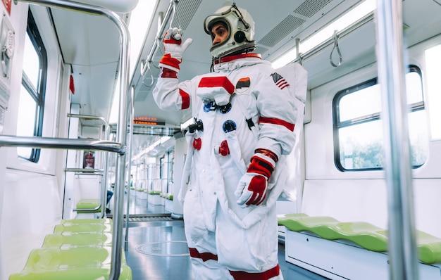 Spaceman na futurystycznej stacji. mężczyzna w skafandrze kosmicznym wychodzący do pracy i wsiadający na pociąg