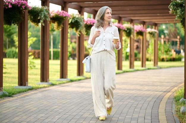 Spacer na łonie natury. medytacyjna elegancka dorosła kobieta w jasnym garniturze z kawą spacerująca w parku w piękny letni dzień
