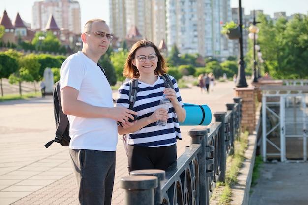 Spacer na świeżym powietrzu mężczyzna i kobieta w odzieży sportowej z plecakami
