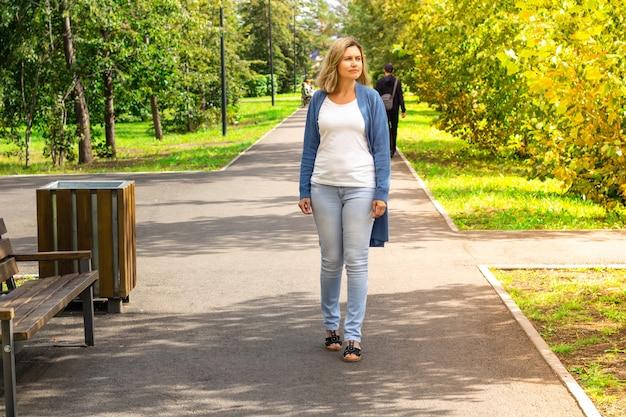 Spacer po parku zalanym słońcem. dojrzała kobieta kaukaski idąc ścieżką. kaukaska kobieta spaceruje wśród drzew i słońca w letni dzień w swetrze. ostatnie dni lata