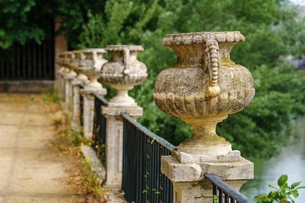 Spacer po publicznym parku wzdłuż rzeki tag i żelazne ogrodzenie ze starożytnymi kamiennymi wazami