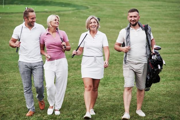 Spacer po trawniku. wesołych przyjaciół spędzających czas na polu golfowym z kijami i dobrym humorem.