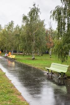 Spacer po ulicach dzielnicy friedrichshain w deszczowy dzień, wielokolorowe ławki parkowe w blankensteinpark