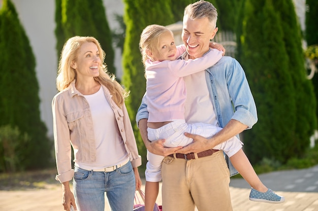 Spacer, rodzina. uśmiechnięta śliczna mała dziewczynka w ramionach troskliwego taty i radosnej uroczej mamy z zakupami spacerującymi po ulicy w słoneczny dzień
