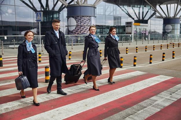 Spacer zespołu samolotu z bagażem na przejściu dla pieszych w pobliżu nowoczesnego lotniska. młode uśmiechnięte kobiety i mężczyzna noszą mundur. stewardesa i stewardesy. praca w zespole. cywilne lotnictwo komercyjne. koncepcja podróży lotniczych