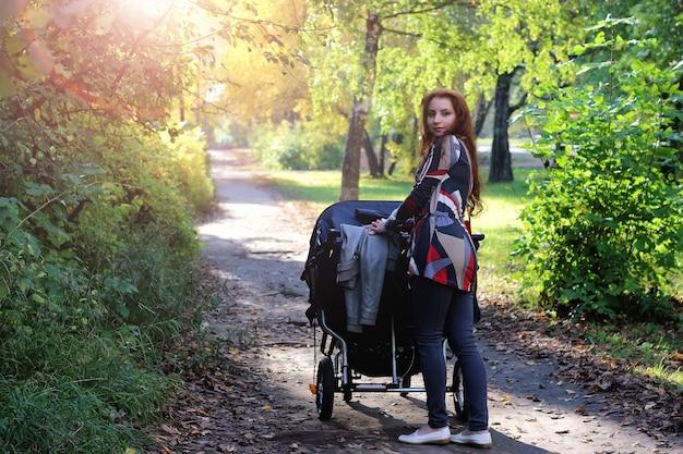 Spaceruj kobiety z wózkiem letnim światłem słonecznym