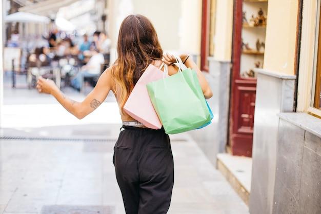 Spacerując kobieta trzyma papierowe torby