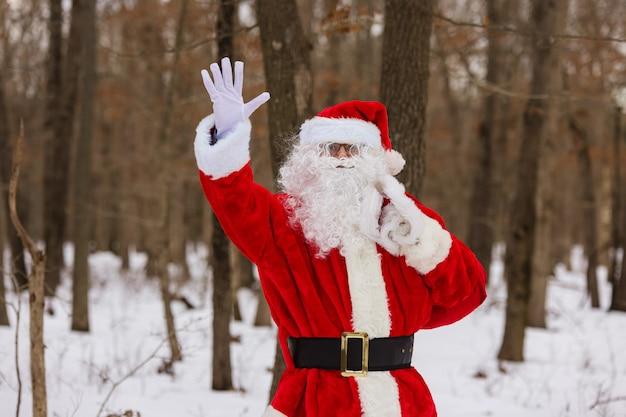Spacerując po zimowym lesie, święty mikołaj macha ręką, niosąc prezenty świąteczne