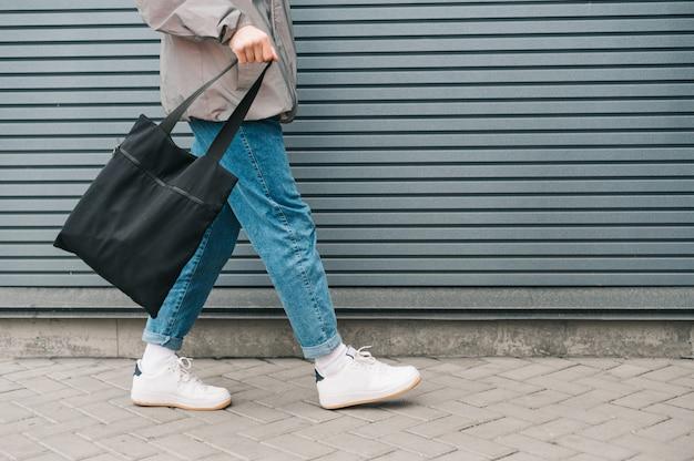 Spaceruje facet w dżinsach i trampkach z eko torbą wielokrotnego użytku w dłoni