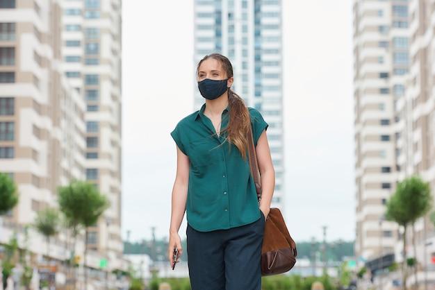 Spaceruje młoda kobieta w medycznej masce, trzymając smartfon i wsuwając drugą rękę do kieszeni spodni