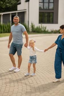Spacery z rodzicami. śliczna dziewczyna w dżinsowej spódnicy spacerująca z rodzicami wieczorem