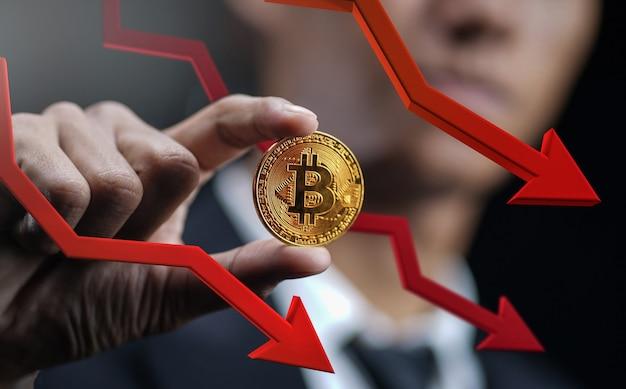 Spadająca cena bitcoinów. biznesmen gospodarstwa bitcoin z czerwoną strzałką 3d w dół