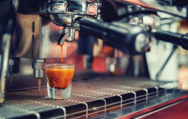 Spadająca kropla kawy w filiżance. przygotuj kawę w ekspresie.