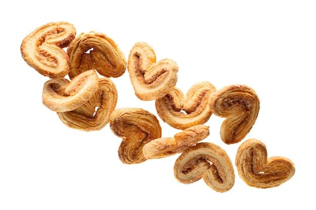 Spadające chrupiące ciasteczka z cukrem i cynamonem, odizolowane na białym tle