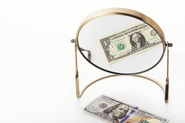 Spadające dochody z powodu pandemicznego koronawirusa covid-19. 100 dolarów odbija się w lustrze jako jeden dolar. pojęcie globalnego kryzysu.