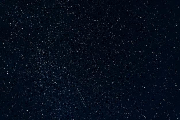 Spadające gwiazdy na gwiaździstym błękicie nocnego nieba z mleczną drogą