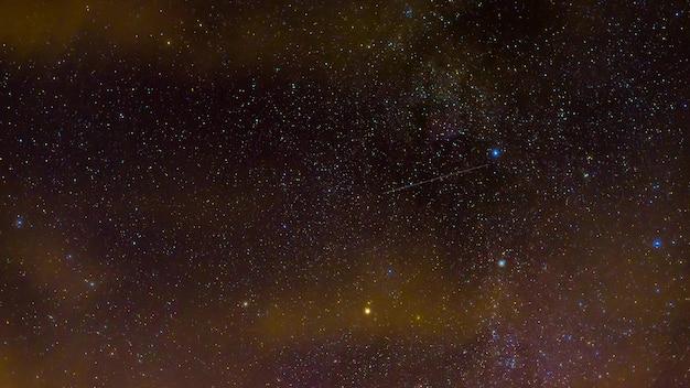 Spadające gwiazdy na tle drogi mlecznej, galaktyki i konstelacje nocą. timelapse nocnego gwiaździstego nieba z chmurami