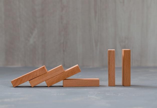 Spadające i stojące drewniane klocki na gipsie i drewnianym stole