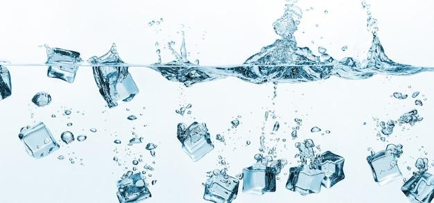 Spadające kostki lodu w rozpryskach wody na białym tle na białej ścianie. kostki lodu rozpryskujące się na powierzchni wody.