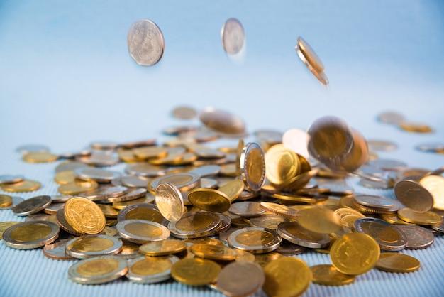 Spadające monety pieniądze na niebieskim tle