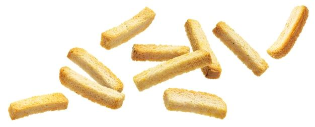 Spadające solone paluszki chlebowe na białym tle