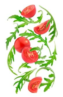 Spadające świeże warzywa. czereśniowi pomidory i rucola odizolowywający na bielu