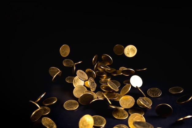 Spadające złote monety pieniądze w ciemnym tle