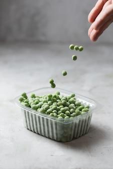 Spadający mrożony zielony groszek w pojemniku na kuchennym stole, orientacja pionowa