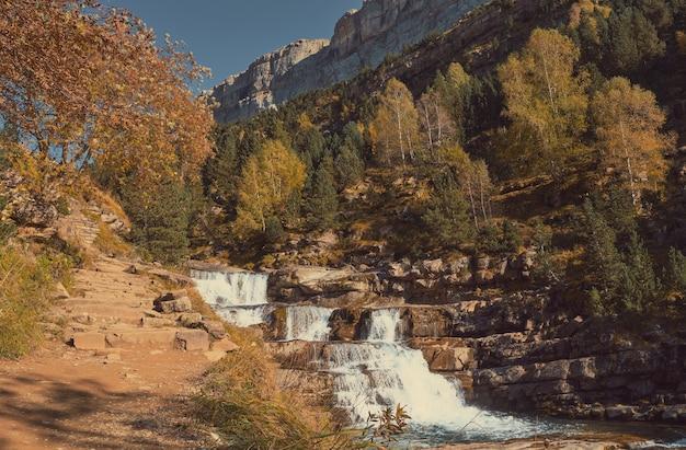 Spadający wodospad po skałach między górami i promieniami słońca