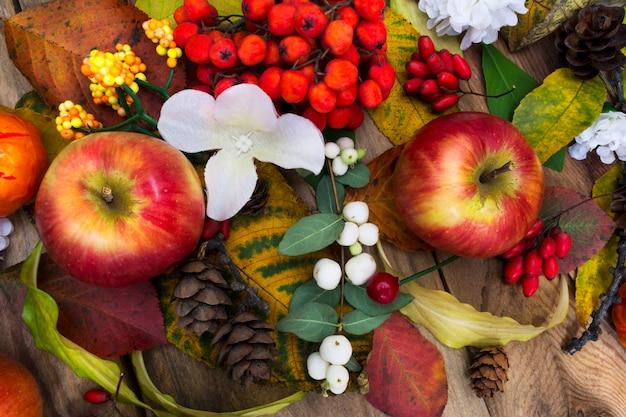Spadek centralny stół z jabłkami i białymi kwiatami jedwabiu, widok z góry