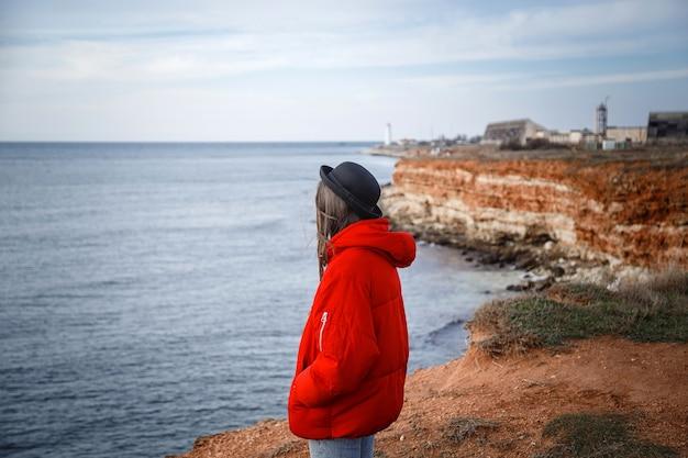 Spadek kobieta w deszczu patrząc na ocean w szary dzień. jasne i radosne na brzegu morza