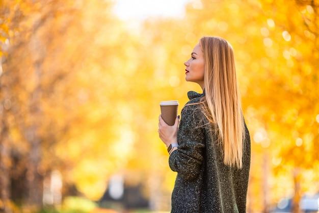 Spadku pojęcie - piękna kobieta pije kawę w jesień parku pod spadku ulistnieniem