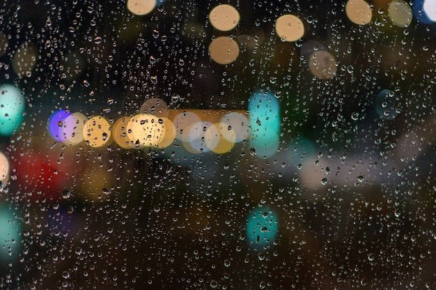 Spadł deszcz na okno. podczas gdy przez okno przechodzi światło jako bokeh.
