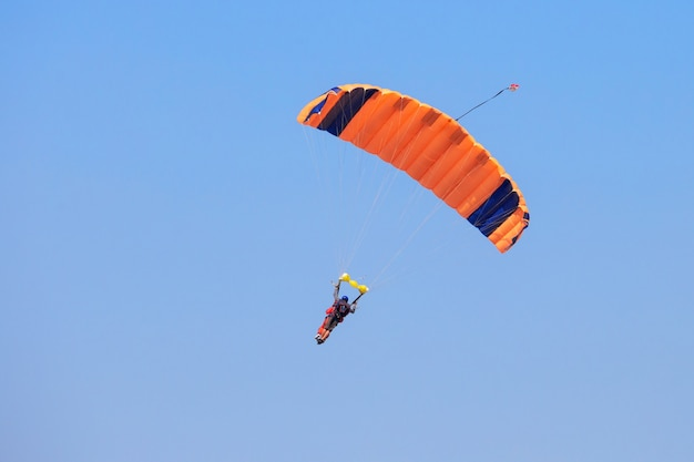 Spadochroniarz pod pomarańczowym spadochronem