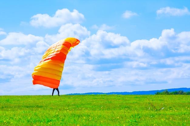 Spadochroniarz wylądował na trawiastym polu. skok ze spadochronem. spadochroniarstwo.