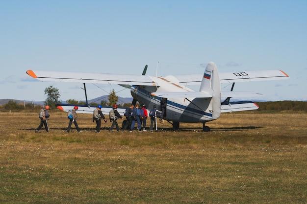 Spadochroniarze wchodzą do dwupłatowca przed skokiem, samolot w polu przed startem latem.