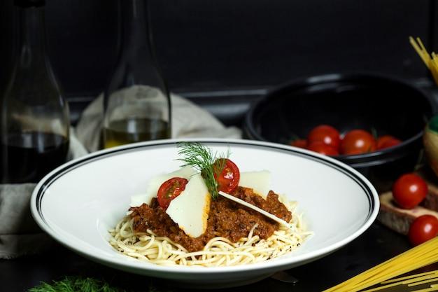 Spaghetti bolońskie przyozdobione pomidorami koktajlowymi i parmezanem