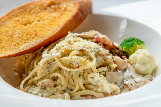 Spaghetti carbonara z bagietką na białym talerzu