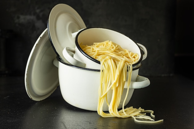 Spaghetti gotowane w rondlu z pszenicy durum danie włoskie ekologiczne, zdrowe danie na stole
