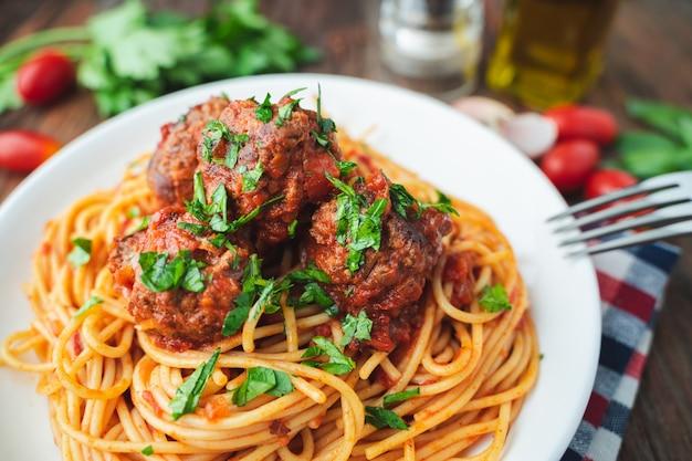 Spaghetti i klopsiki z pomidorowym kumberlandem w białym naczyniu na drewnianym wieśniaku wsiadamy